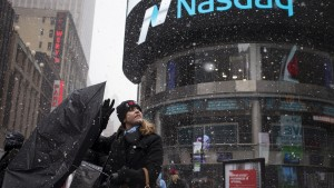 A woman's umbrella turns inside out as she walks past the Nasdaq MarketSite during a snow storm in Times Square, Midtown New York