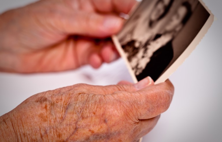Elderly hands holding photograph