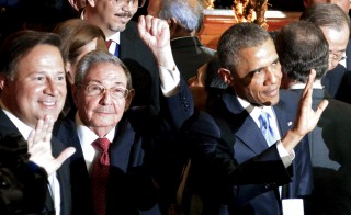 Cuba's President Raul Castro (C) holds up his left fist as his Panamanean and U.S. counterparts Juan Carlos Varela (L) and Barack Obama (R) wave before the inauguration of the VII Summit of the Americas in Panama City April 10, 2015, in this handout photo provided by the Presidency of Cuba. The presidents will be holding a meeting for the first time in more than 50 years. Photo by Presidency of Cuba/Handout via Reuters.