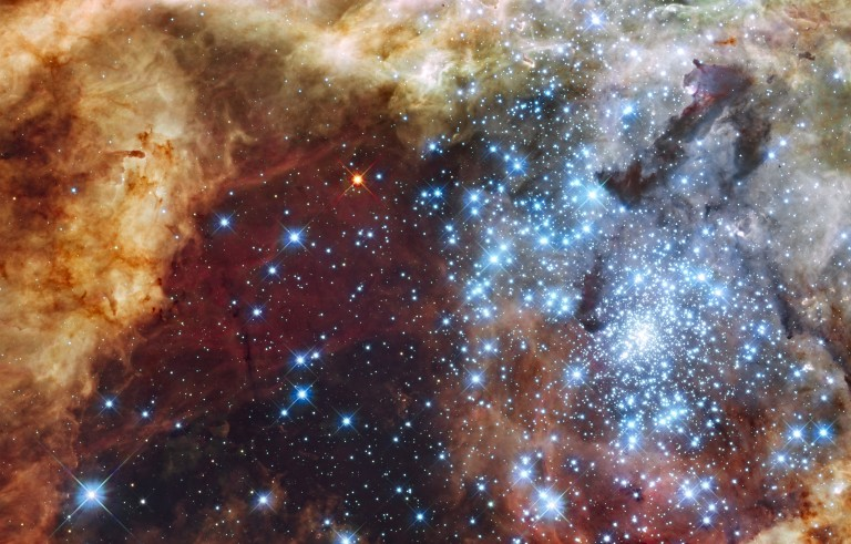 The massive, young stellar grouping, called R136, is only a few million years old. Many of the diamond-like icy blue stars are among the most massive stars known. Several of them are over 100 times more massive than our Sun. These hefty stars are destined to pop off, like a string of firecrackers, as supernovae in a few million years. Photo by NASA, ESA, F. Paresce (INAF-IASF, Bologna, Italy), R. O'Connell (University of Virginia, Charlottesville), and the Wide Field Camera 3 Science Oversight Committee