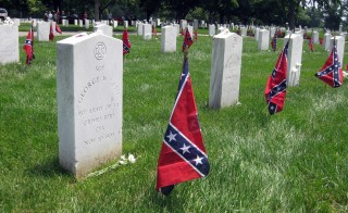 Confederate battle flags stand next to graves of soldiers in the Confederate section of Arlington National Cemetery. Today, a handful of Southern states  mark Confederate Memorial Day as a state holiday.  Photo by  Wally Gobetz/Flickr.