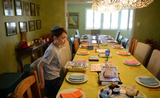 Nine-year-old Remy Eidelman surveys the table decoration for his family's upcoming Passover seder dinner  in Potomac, Maryland on April 2, 2015. Photo by Astrid Riecken For The Washington Post via Getty Images