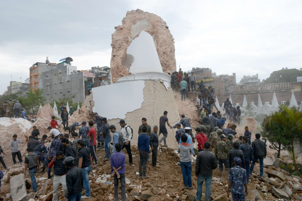 Nepalese rescuers and onlookers gather at the collapsed Dharahara Tower in Kathmandu on April 25, following a 7.8-magnitude earthquake. Photo by Prakash Mathema/AFP/Getty Images