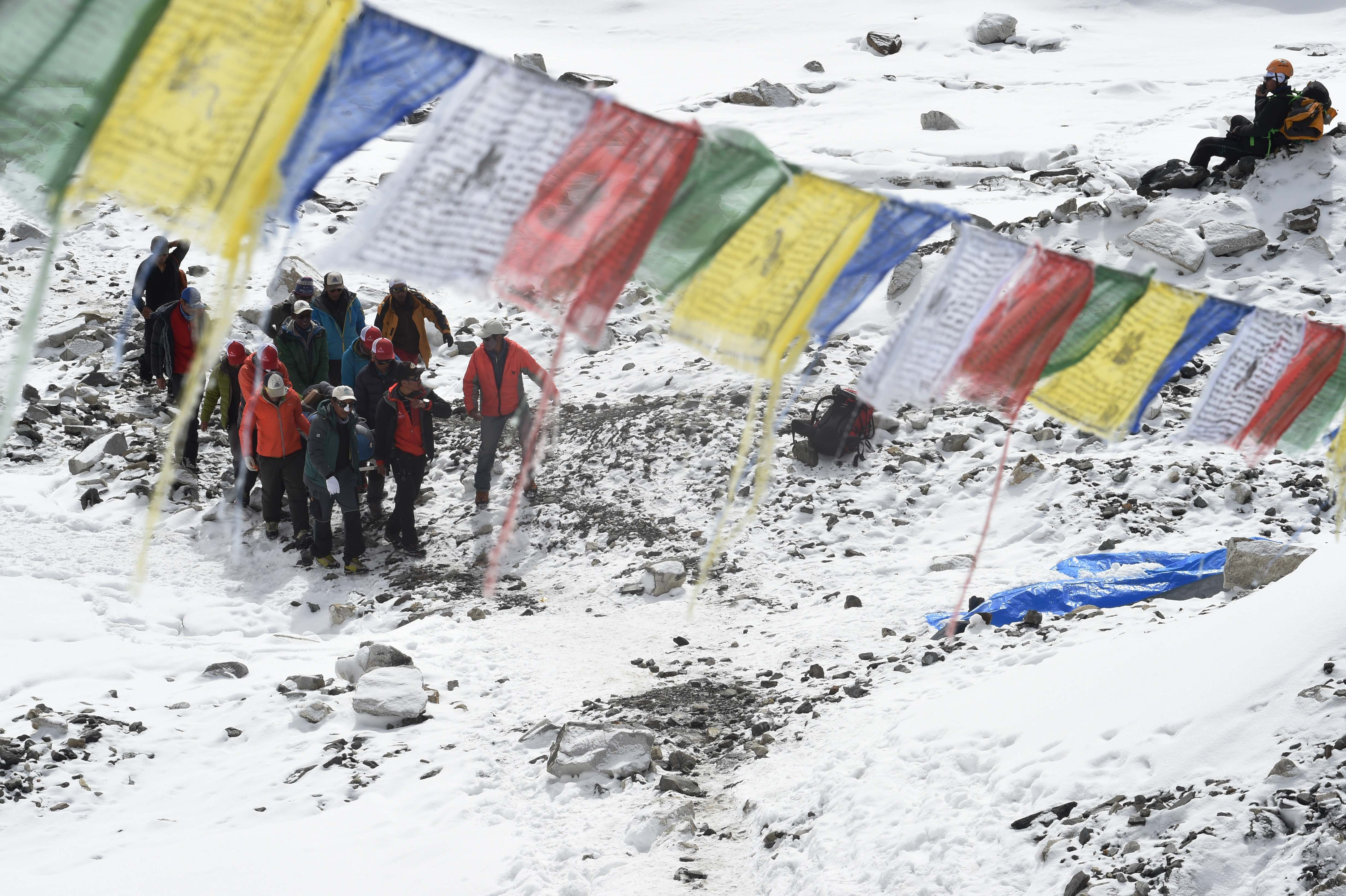 Rescue team personnel carry an injured person towards a waiting rescue helicopter at Everest Base Camp on April 26, 2015, a day after an avalanche triggered by an earthquake devastated the camp.  Photo by Roberto Schmidt/AFP/Getty Images.