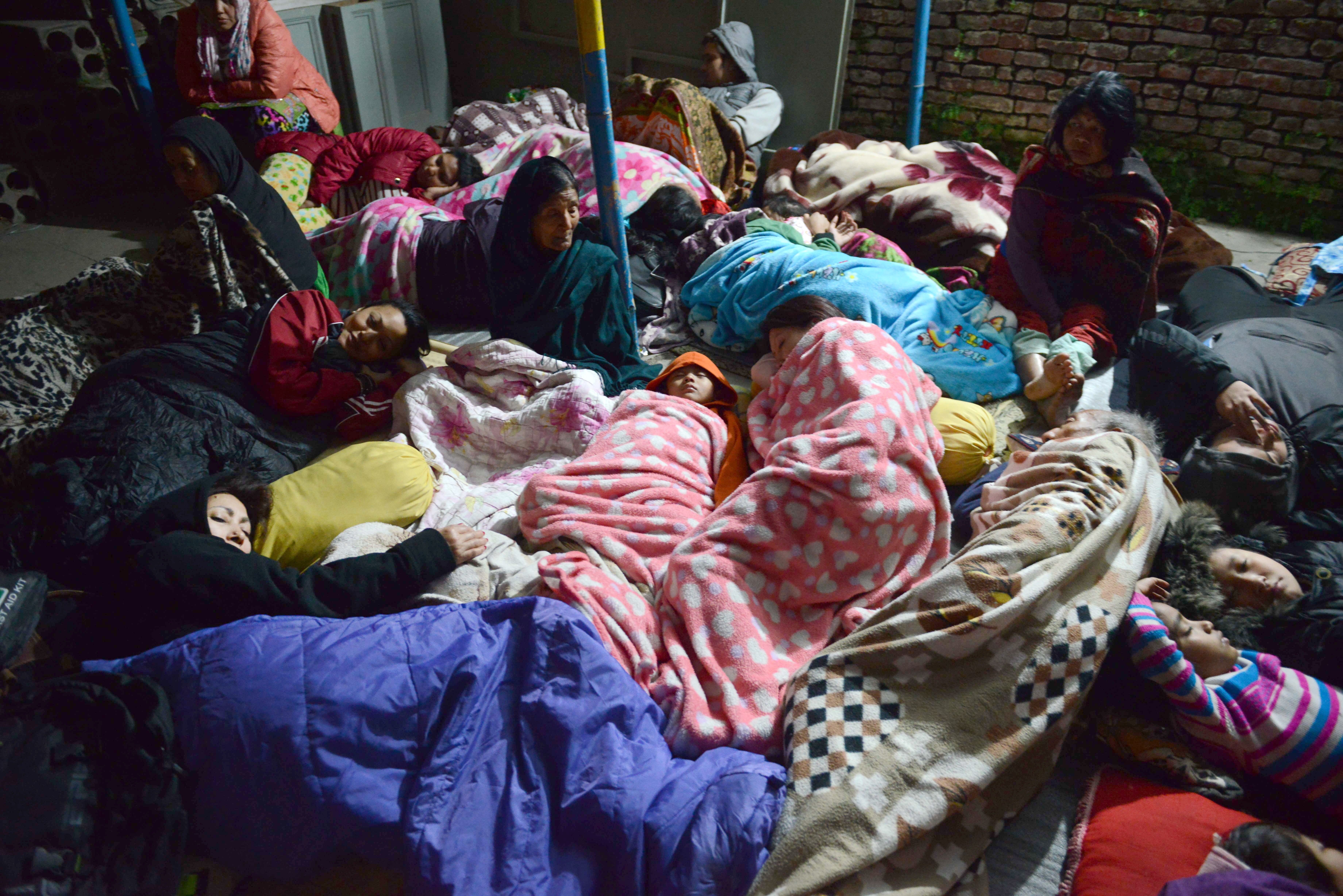 Nepalese residents sleep in an open area in Kathmandu on April 26, 2015, after an earthquake hit the Kathmandu Valley. Photo by Prakash Mathema/AFP/Getty Images.