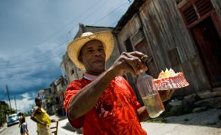 A Cuban man, holding a bottle of rum, smoking a cigar and carrying a cake, heads to a fiesta in Santiago de Cuba, Cuba. Photo by Jan Sochor via Getty Images