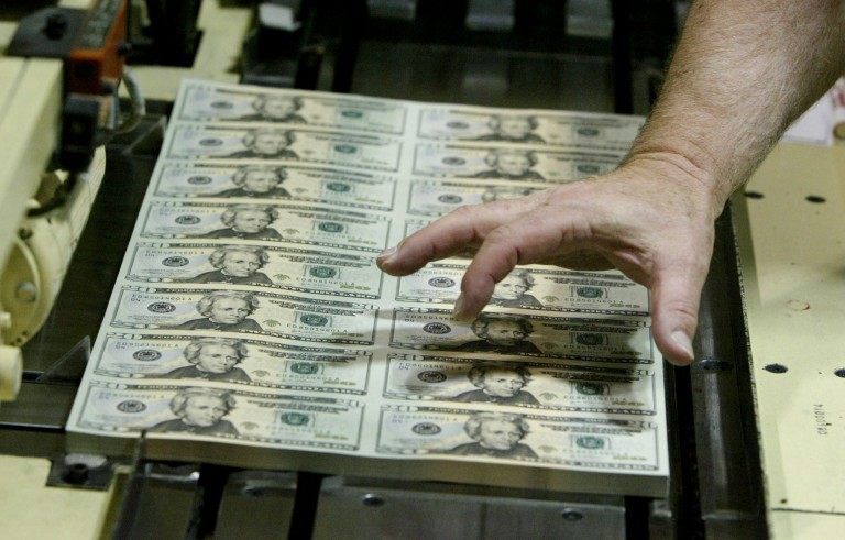 An employee checks sheets of the newly-designed $20 bill, coming off the printing press at the U.S. Bureau of Engraving and Printing Western Facility in Fort Worth, Texas on Aug. 19, 2003. Photo by Jeff Mitchell/Reuters
