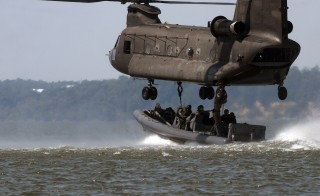 U.S. Navy Special Warfare troops rig their rigid-hull inflatable boat to a CH-47 Chinook helicopter during a training exercise near Fort Eustis, Virginia, July 16, 2008. Surveys find that men in U.S. special operations forces do not believe women can meet the physical and mental demands of their commando jobs. Photo by Robyn Gerstenslager/U.S. Navy/Reuters