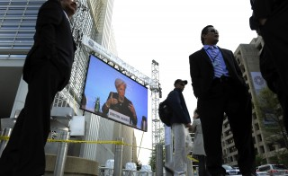 Head of the International Monetary Fund, Christine Lagarde (C) appears on an outdoor television screen during a news conference after a day of meetings with G-20 finance ministers and central bank governors at the IMF and World Bank Spring Meetings in Washington on April 15, 2011. Photo by Jonathan Ernst/Reuters