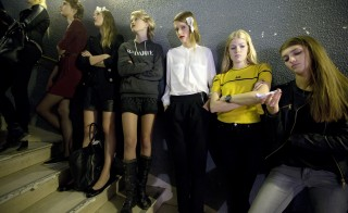 Models wait for the start of a rehearsal before the presentation of French designer Jean-Charles Castelbajac Spring/Summer 2014 women's ready-to-wear collection in Paris