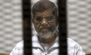 Ousted Egyptian President Mohamed Morsi is seen behind bars during his trial in Cairo on May 8, 2014.  Photo by Reuters stringer