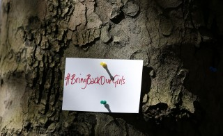 A sign is seen pinned to a tree during a demonstration against the kidnapping of school girls in Nigeria, outside the Nigerian Embassy in London