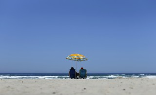 A couple sits under an umbrella for shade from the sun at the beach in La Jolla, California May 12, 2014. A high pressure system is expected to bring record breaking heat to Southern California over the next few days.   REUTERS/Mike Blake    (UNITED STATES - Tags: ENVIRONMENT TPX IMAGES OF THE DAY) - RTR3OUQ2