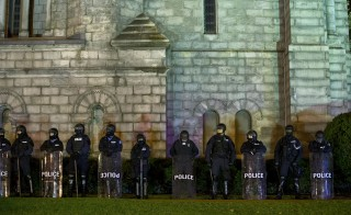 Police stand guard during a protest at Cathedral Basilica, after a man was fatally shot by a policeman, in St. Louis, Missouri, December 25, 2014. Whites in the United States approve of police officers hitting people in far greater numbers than blacks and Hispanics do, according to a recent survey. Photo by Aaron P Bernstein/Reuters