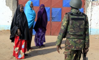 A Kenya Defense Force soldier stops women from moving in the direction where attackers are holding up at a campus in Garissa on April 2. Photo by Noor Khamis/Reuters