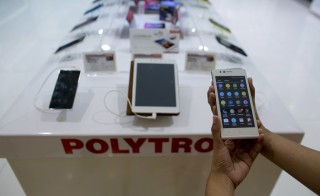 An employee at a Polytron showroom displays a Zap5 4G ready smartphone in a shopping mall in Jakarta