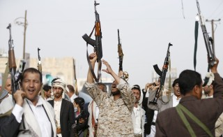 Followers of the Houthi movement raise their rifles as they shout slogans against the Saudi-led air strikes in Sanaa