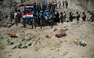 Iraqi soldiers salute as they stand next to a mass grave for Shi'ite soldiers from Camp Speicher who have been killed by Islamic State militants in the presidential compound of the former Iraqi president Saddam Hussein in Tikrit