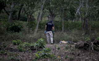 A police investigator works at a crime scene where five suspected gang members were killed in the town of Chalchuapa April 7, 2015. The five suspected gang members were killed by armed men after they were taken from their homes during the night, simulating a police raid and executed, according to local media. Photo by REUTERS/Jose Cabezas.