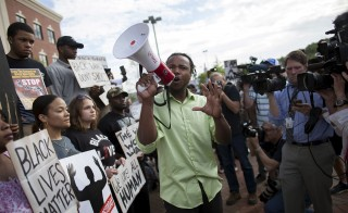 Muhiydin Moye D'Baha of the Black Lives Matter movement leads the protest at a rally in North Charleston, South Carolina April 8, 2015. Demonstrators rallied on Wednesday against what they described as a culture of police brutality in South Carolina in the case of white officer Michael Slager, who was caught on video killing 50-year-old Walter Scott, a black man, by shooting him in the back as Scott ran away after a traffic stop. Slager was charged on Tuesday with murder in the death of Scott.   REUTERS/Randall Hill  - RTR4WJS3