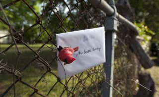 A note for the Scott family is seen at a small memorial for Walter Scott in North Charleston, South Carolina April 9, 2015. Residents are in mourning against what they feel is a culture of police brutality in South Carolina in the case of white officer MIchael Slager, who was caught on video killing 50-year-old Scott, a black man, by shooting him in the back as Scott ran away after a traffic stop. Slager was charged on Tuesday with murder in the death of Scott.   REUTERS/Randall Hill  - RTR4WPLO