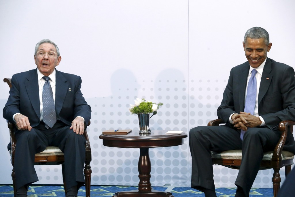 U.S. President Barack Obama smiles during a meeting with Cuba's President Raul Castro, who listens to a translator, during the first plenary session of the Summit of the Americas in Panama City, Panama April 11, 2015. Obama and Castro shook hands on Friday at the summit, a symbolically charged gesture as the pair seek to restore ties between the Cold War foes. REUTERS/Jonathan Ernst - RTR4WY36