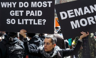 A protester holds signs in front of a McDonald's restaurant during demonstrations for higher wages in the Manhattan borough of New York City in April 2015. Image by Reuters/Lucas Jackson
