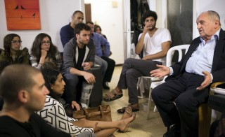 "Dov Landau, an 88-year-old Auschwitz survivor, speaks to people during an informal gathering commemorating Holocaust Remembrance Day in Tel Aviv, Israel on April 15, 2015. Five years ago, a group of youngsters began ""Memories@Home,"" a project whereby a Holocaust survivor is invited to speak in the lounge of a willing host and thereby commemorate the annual memorial day in an intimate setting. Photo by Amir Cohen/Reuters"