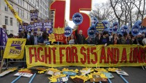 Demonstrators hold signs during demonstrations asking for higher wages in the Manhattan borough of New York