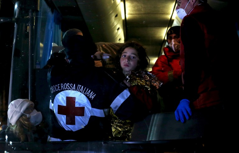 A child is carried into bus as migrants arrive via boat at the Sicilian harbor of Pozzallo
