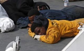 Surviving immigrants lie on the deck of the Italian coastguard ship Bruno Gregoretti in Valletta's Grand Harbour Monday. The Italian patrol ship arrived in Malta with 24 corpses recovered out of hundreds feared drowned after a migrant boat capsized in the Mediterranean, in one of the worst disasters yet in a growing humanitarian crisis. Photo by Darrin Zammit Lupi/Reuters