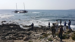 Greek Coast guard officers and locals look at a capsized sailboat with migrants onboard, who are trying to reach Greece, near the coast of the southeastern island of Rhodes