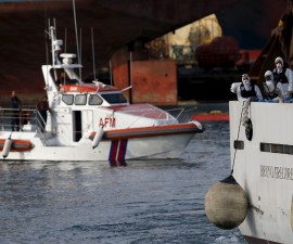 Italian coastguard personnel in protective clothing stand on the deck of their ship 'Bruno Gregoretti', carrying dead immigrants on board, as it arrives in Senglea