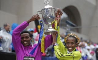 Men's division winner Lelisa Desisa of Ethiopia, left, and women's division winner Caroline Rotich of Kenya pose with the trophy at the finish line of the 119th Boston Marathon in Boston, Massachusetts April 20, 2015. Photo by Brian Snyder/Reuters