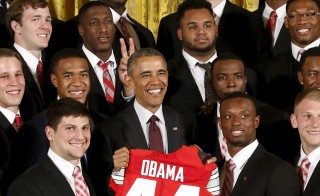 Ohio State Buckeyes team captain Michael Bennett -- top row, second right -- holds his fingers behind U.S. President Barack Obama's head during a photo as Obama plays host to the reigning NCAA football champion Buckeyes in a reception at the East Room of the White House in Washington, April 20, 2015. Photo by Jonathan Ernst/Reuters