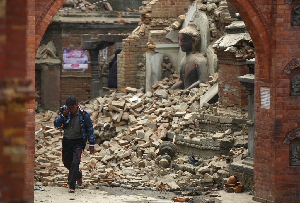 A man passes a damaged statue of Lord Buddha in Bhaktapur, Nepal, a day after an earthquake struck central Nepal on April 25. Photo by Navesh Chitrakar/Reuters