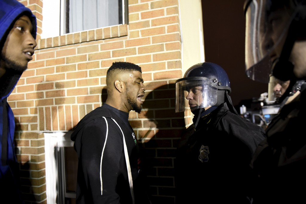 Demonstrators confront law enforcement officers near Baltimore Police Department Western District to protest against the death of Freddie Gray in police custody, in Baltimore April 25, 2015. Thousands of people marched peacefully through downtown Baltimore on Saturday to protest the unexplained death of the 25-year-old black man in police custody but pockets of violence erupted when a small group smashed windows and threw bottles at officers.  REUTERS/Sait Serkan Gurbuz - RTX1AAU6