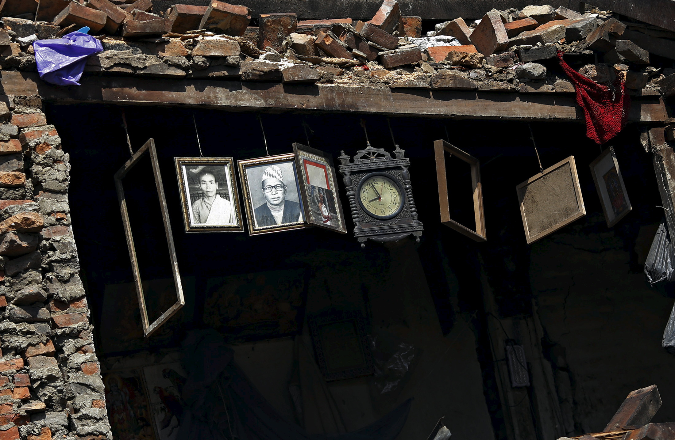 Framed photographs and a clock are seen hanging inside a damaged house after Saturday's earthquake in Bhaktapur, Nepal, on Monday. Photo by Adnan Abidi/Reuters