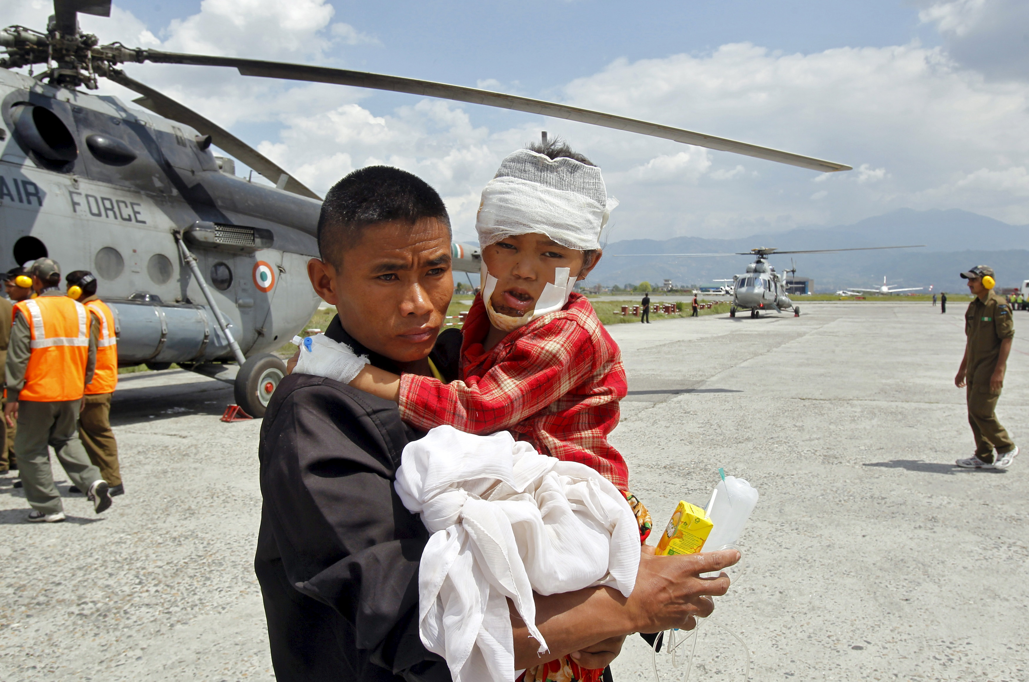 A man carries a child, who was wounded in Saturday's earthquake, after Indian Army soldiers evacuated them from Trishuli Bazar to the airport in Kathmandu, Nepal, on Monday. Photo by Jitendra Prakash/Reuters