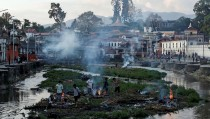 Victims of Saturday's earthquake are cremated along a river in Kathmandu