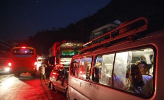 People ride on a van as traffic is affected by a landslide caused by an earthquake, in Kurintar