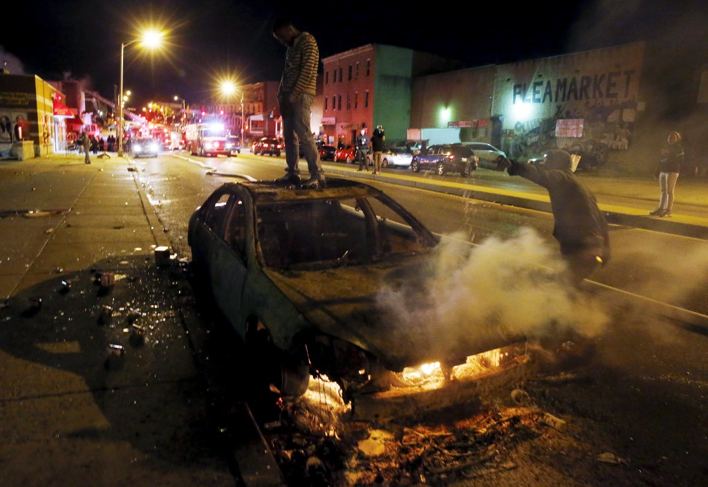 A rioter stands atop a burning car while Baltimore firefighters attend to multiple burning buildings set ablaze by rioters during clashes in Baltimore Monday night. Maryland Governor Larry Hogan declared a state of emergency and activated the National Guard to address the violence in the city after the funeral of a black man, Freddie Gray, who died in police custody. Photo by Jim Bourg/Reuters