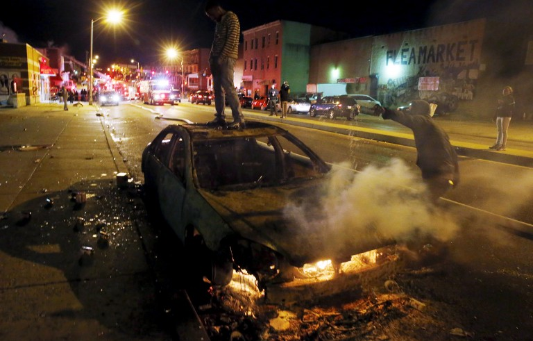 A rioter stands atop a burning car while Baltimore firefighters attend to multiple burning buildings set ablaze by rioters during clashes in Baltimore on April 27. Photo by Jim Bourg/Reuters