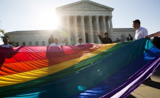 Gay marriage supporters hold a gay rights flag in front of the U.S. Supreme Court before a hearing about gay marriage