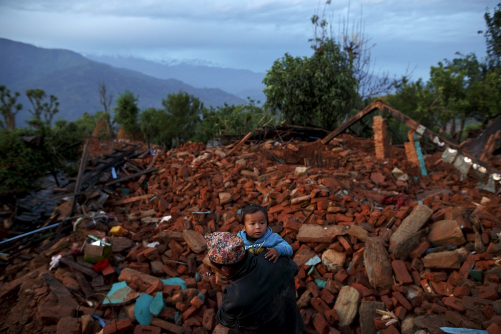 A local villager walks carrying a child amid debris at a devastated area following Saturday's earthquake, at Paslang village in Gorkha, Nepal April 28, 2015. Photo by Athit Perawongmetha