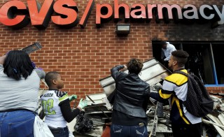 Members of the community work to clean up a recently looted and burned CVS store in Baltimore, Maryland, United States April 28, 2015. Photo by Jim Bourg/Reuters