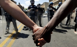 Members of the community hold hands in front of police officers in riot gear outside a recently looted and burned CVS store in Baltimore, Maryland on April 28, 2015. Photo by Jim Bourg/Reuters