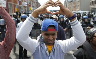 A member of the community makes a heart gesture with his hands in front of a line of police officers in riot gear, near a recently looted and burned CVS store in Baltimore, Maryland, April 28, 2015. Baltimore's mayor came under criticism on Tuesday for a slow police response to some of the worst urban violence in the United States in years in which shops were looted, buildings burned to the ground and 20 officers were injured.REUTERS/Jim Bourg