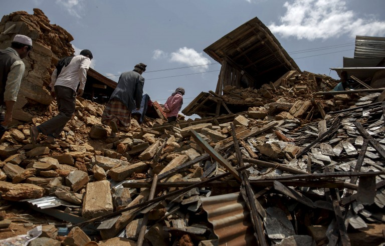 local villagers walk amid debris at a devastated area following Saturday's earthquake, at Asslang village, in Gorkha