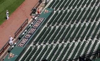 A Baltimore Orioles player stands in the dugout and looks at empty seats before the start of their American League baseball game Chicago White Sox American League baseball game at Camden Yards baseball stadium in Baltimore, Maryland